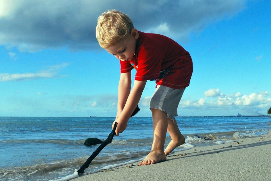 Niño jugando con un palo en la playa